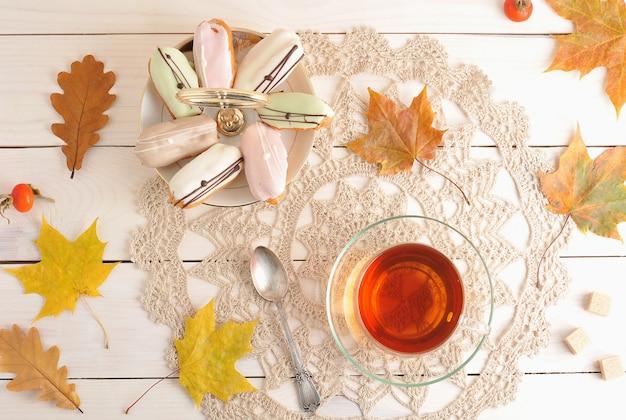 Bolo em um prato e chá em uma caneca transparente com colher e folhas de outono