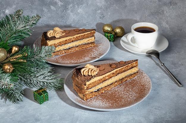 Bolo festivo com camada intermediária de chocolate e crocante. duas porções. sobre um fundo cinza. aniversário, feriados, doces. copie o espaço.