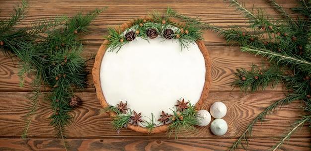 Bolo festivo com creme branco decorado com cones, ramos de coníferas e anis estrelado. conceito de ano novo e natal. copie o espaço e a vista superior.