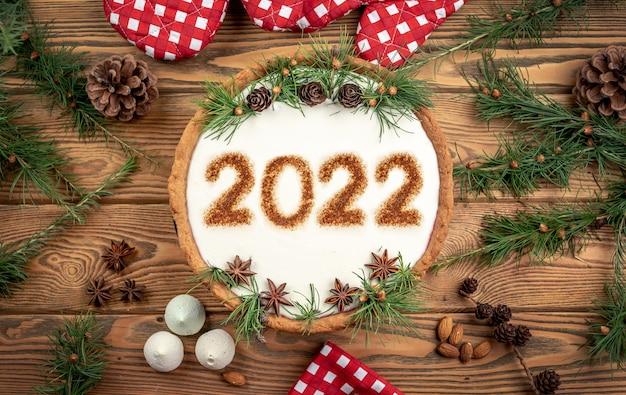 Bolo festivo com os números 2022 em creme branco, decorado com cones, ramos de coníferas e anis estrelado. conceito de ano novo.