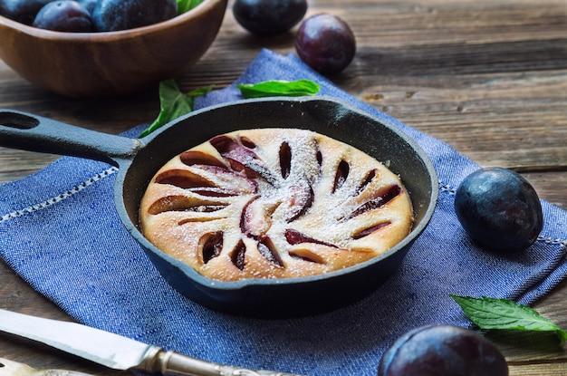 Bolo fresco de ameixa caseiro em frigideira de ferro com fundo de madeira rústica.