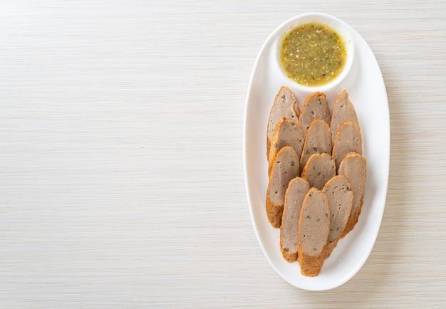 Bolo frito de peixe chinês ou linha de bolinho de peixe fatiado com molho picante de frutos do mar
