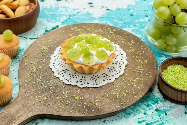 Bolo gostoso com creme delicioso e biscoitos de uvas frescas e fatiados na mesa de luz azul
