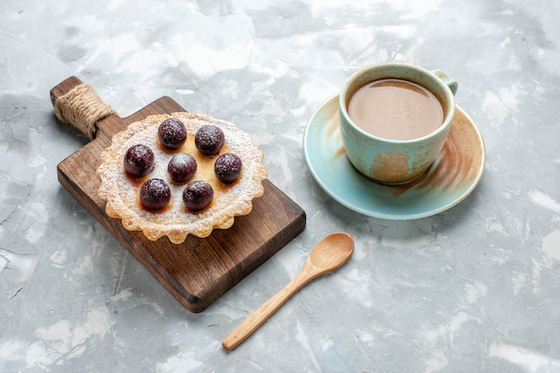 Bolo gostoso com frutas açucaradas em pó e café com leite na luz, bolo biscoito bolo doce