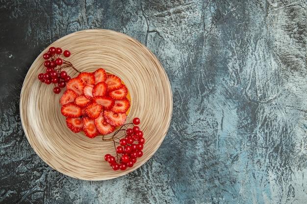 Bolo gostoso de morango com frutas vermelhas em fundo escuro, vista de cima