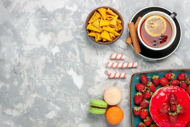 Bolo gostoso de morango com morango vermelho fresco, xícara de chá e macarons no fundo branco.