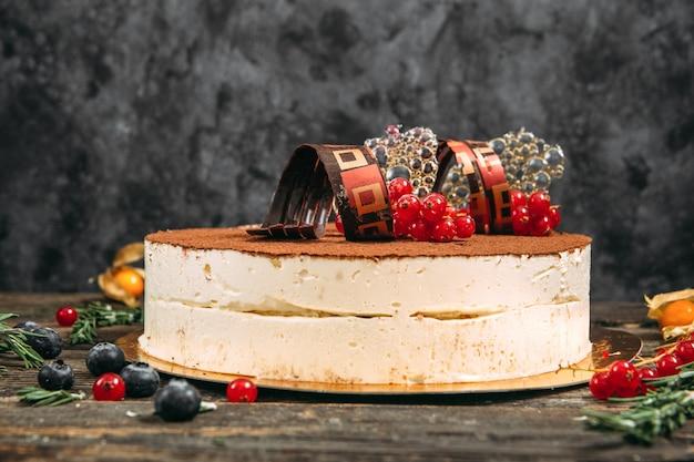 Bolo gourmet com elementos decorativos e frutas