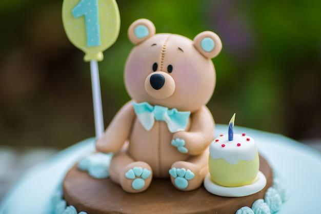 Bolo incrível para o primeiro aniversário do menino. cores azuis e brancas com filhote de urso de mástique de açúcar