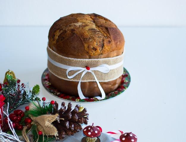 Bolo italiano do natal do panetone do chocolate com decorações da quinquilharia, velas, pinhas ,.
