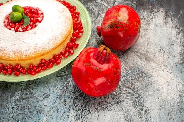 Bolo lateral de close-up com romãs romãs maduras e o prato de um bolo apetitoso