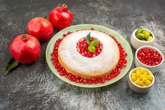 Bolo lateral de close-up com tigelas de romã com frutas vermelhas, um bolo apetitoso e três romãs