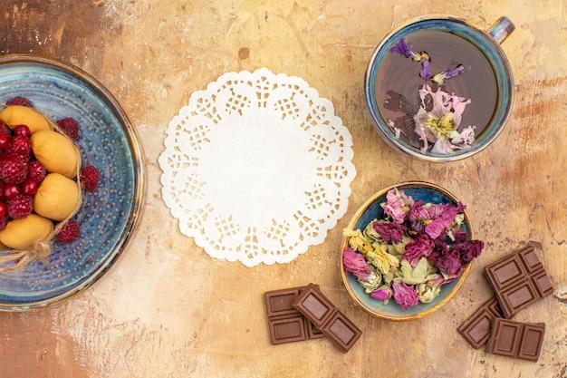 Bolo macio de chá quente de ervas com frutas, flores, barras de chocolate e guardanapo na mesa de cores misturadas