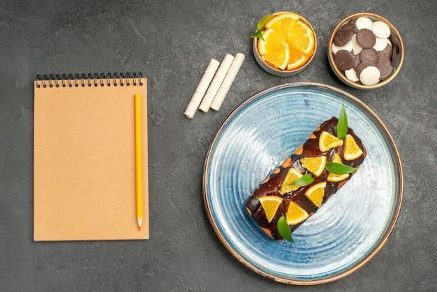 Bolo macio decorado com laranja e chocolate ao lado do caderno na mesa escura