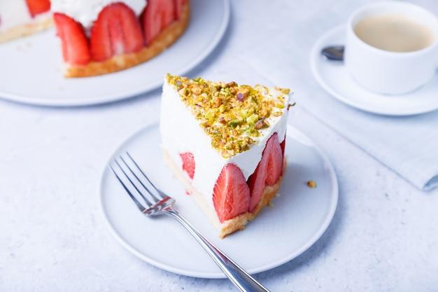 Bolo mais livre com morangos frescos e pistache. sobremesa clássica francesa. porção de bolo em um close-up de placa branca.