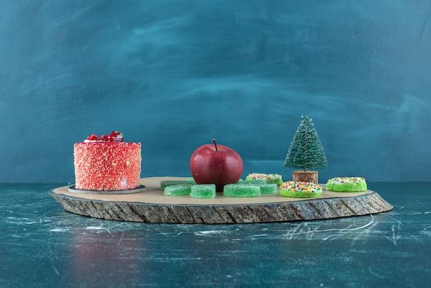 Bolo, marmeladas, donuts e uma maçã em uma placa em azul.