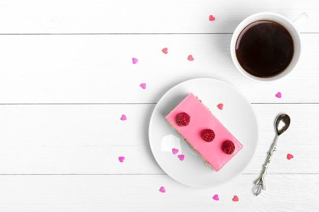 Bolo mousse de morango, café americano, doces corações em fundo branco de madeira