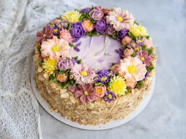 Bolo napoleão com creme de baunilha, decorado com flores de creme de manteiga