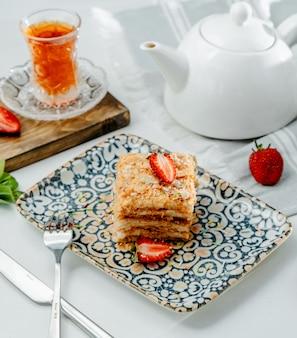Bolo napoleão com morango em cima da mesa