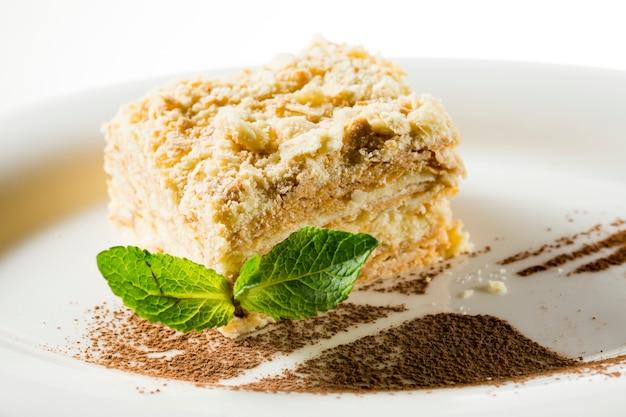 Bolo napoleão com uma folha de hortelã no prato decorado com chocolate