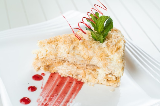 Bolo napoleão decorado com uma espiral de chocolate vermelho, hortelã e geléia de frutas vermelhas em um prato branco. bolo em camadas com creme de confeitaria.
