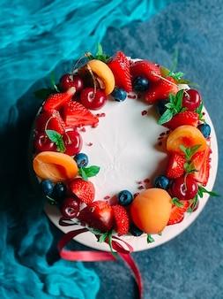 Bolo nu com creme, decorado com frutas vermelhas.