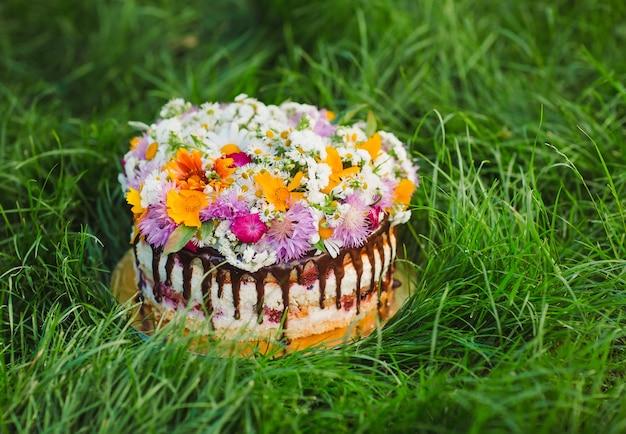 Bolo nu decorado com flores na grama.