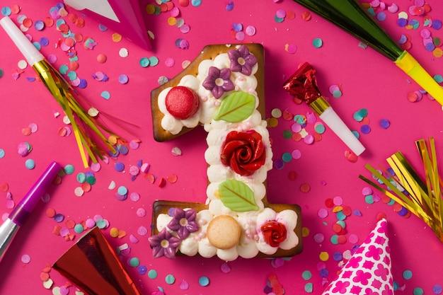 Bolo número um decorado com flores e biscoitos na superfície rosa.