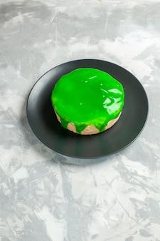 Bolo pequeno com cobertura verde na mesa branca de frente