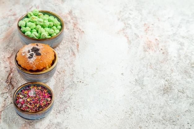 Bolo pequeno com doces em um biscoito de mesa branco