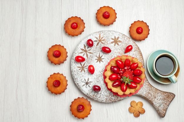 Bolo pequeno com frutas e bolos na mesa branca de cima