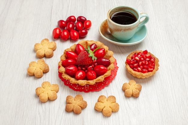 Bolo pequeno com frutas e uma xícara de chá no bolo de sobremesa de frutas de mesa de frente