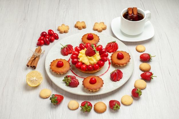 Bolo pequeno com frutas e xícara de chá na mesa branca bolo de sobremesa de frutas de vista frontal