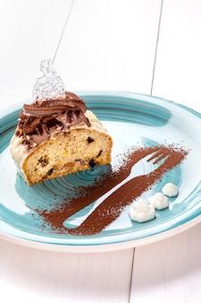 Bolo pequeno com recheio diferente num prato azul. mesa de madeira branca. ainda vida. copie o espaço