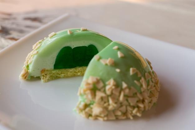 Bolo pequeno com recheio verde. sobremesa glaceada com decoração. biscoito macio e geleia. sabor de hortelã.