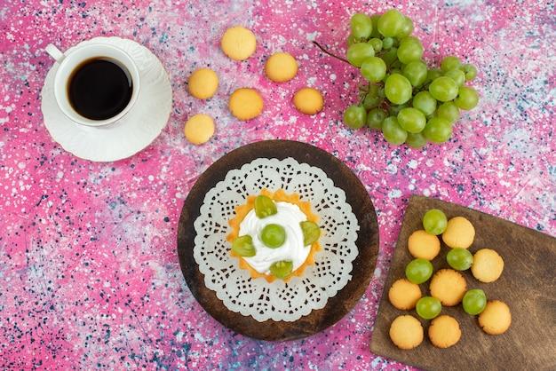 Bolo pequeno com uma xícara de biscoitos de chá e uvas verdes na superfície brilhante do bolo de frutas