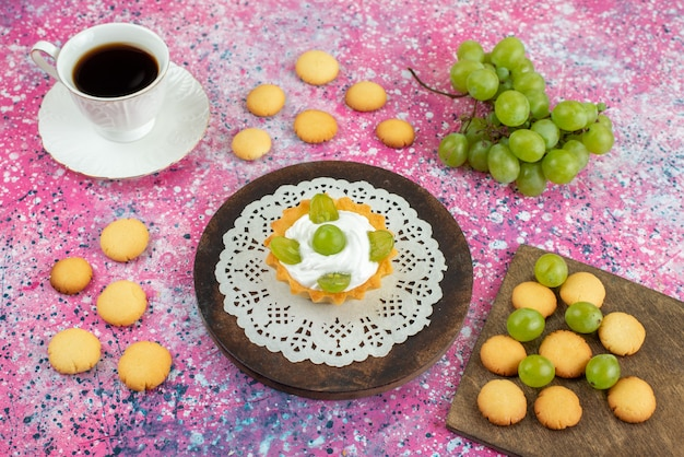 Bolo pequeno com uma xícara de biscoitos de chá e uvas verdes na superfície brilhante.
