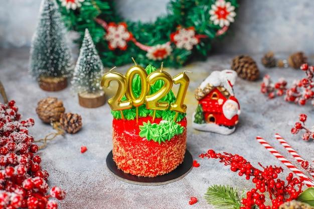 Bolo pequeno de natal decorado com doces figuras de árvore de natal, papai noel e velas.