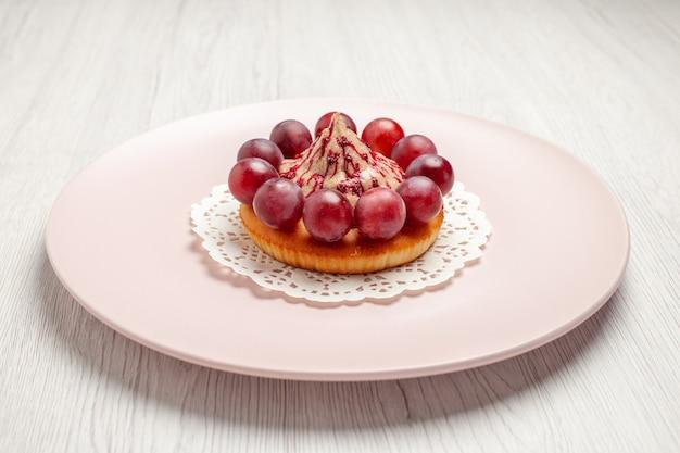 Bolo pequeno de vista frontal com uvas dentro do prato no fundo branco