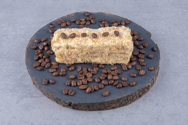 Bolo pequeno e grãos de café em uma placa de madeira sobre mármore
