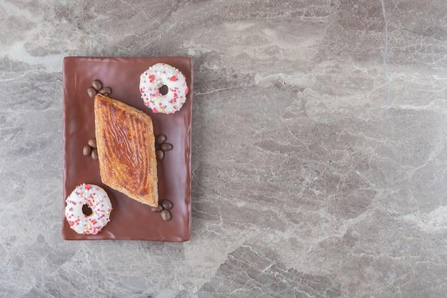 Bolo pequeno, grãos de café e donuts pequenos em uma travessa na superfície de mármore