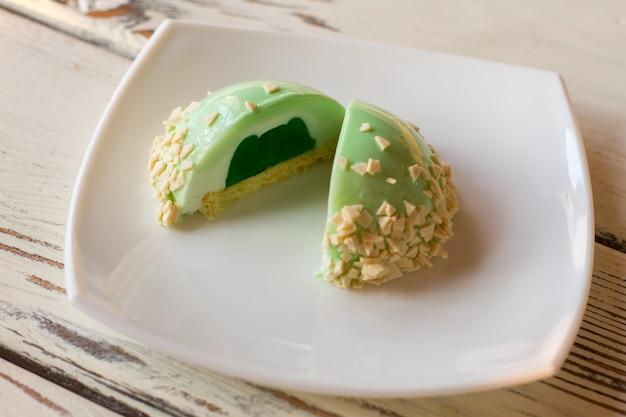 Bolo pequeno verde com recheio. sobremesa glaceada em chapa branca. bolo de mousse de menta acabado de cozer. que tal alguns doces.