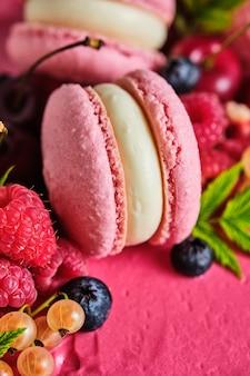 Bolo quadrado rosa decorado com macarons e frutas frescas. bolo para o feriado. a sobremesa é decorada com framboesas frescas, groselhas brancas, cerejas e mirtilos.