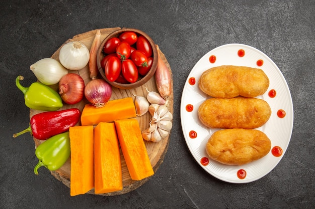 Bolo quente de batata dentro do prato com vegetais em fundo cinza escuro