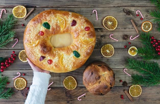 Bolo rei e panetone sobre base de madeira com enfeites de natal. sobremesa de reis e panetone. comida típica. vista do topo.