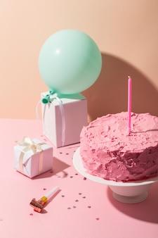 Bolo rosa e arranjo de velas