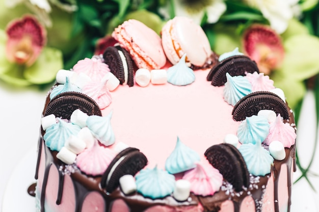Bolo rosa e azul decorado com biscoitos, merengues e macaroons, com manchas de cobertura de chocolate.