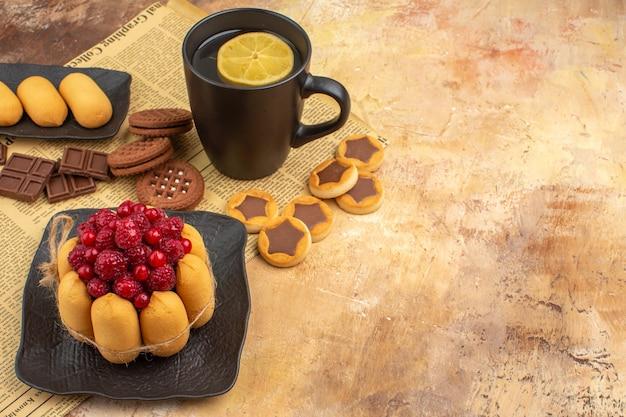 Bolo saboroso, biscoitos e chá em uma xícara preta na mesa de cores diferentes