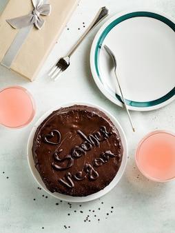 Bolo sacher de chocolate festivo vegan com geleia de damasco em cima da mesa.