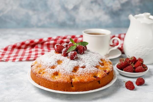 Bolo simples com açúcar de confeiteiro e framboesas frescas em uma luz. sobremesa de verão berry.