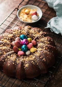 Bolo surpreendente de easter com chocolate e ovos da páscoa coloridos no fundo escuro.